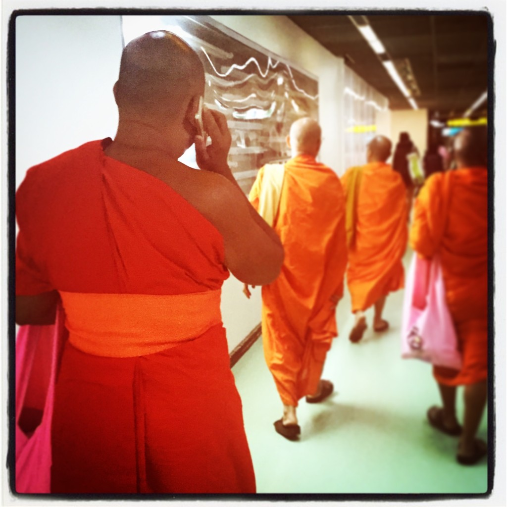 Monk meets new age technology. Photo from Bangkok Airport.