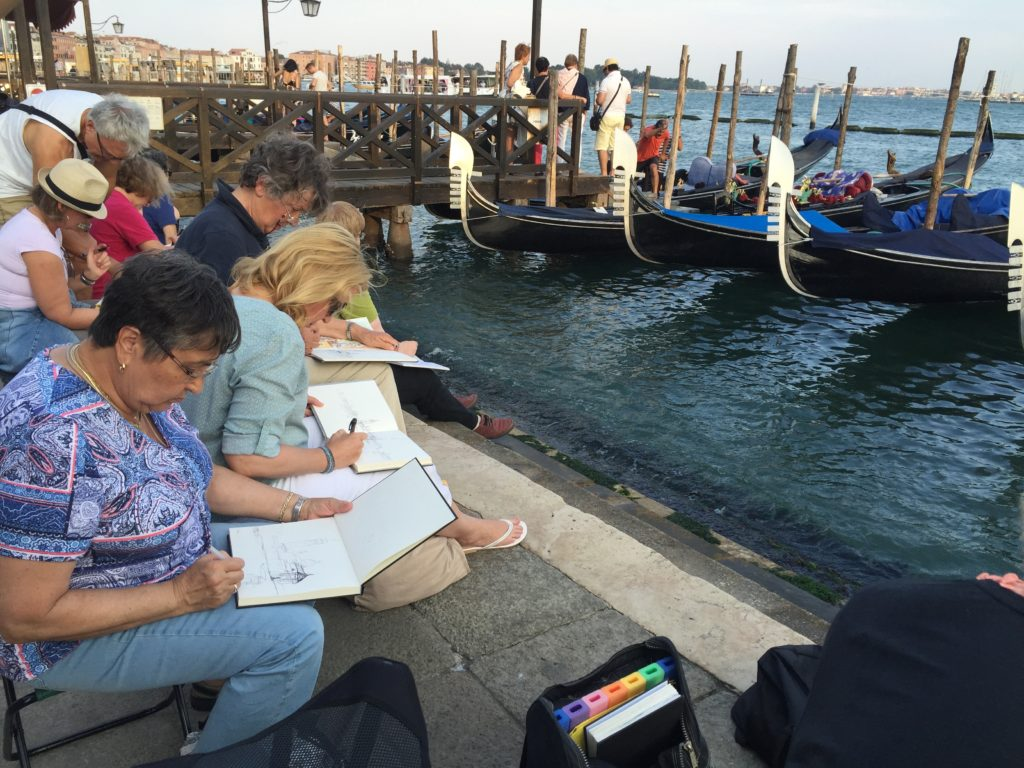 Artists in Venice, Italy create by the waterfront.